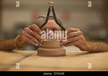 Close up of carpenter measuring turning wood in workshop - Stock Photo