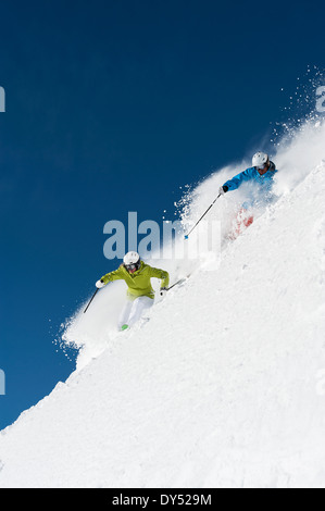 Male and female skiers racing downhill, Obergurgl, Austria - Stock Photo