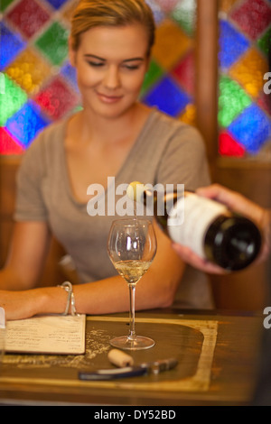Waiter pouring glass of white wine for a young woman - Stock Photo
