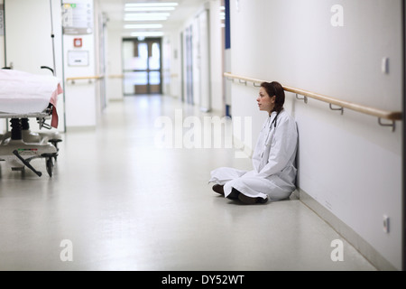 Female doctor sitting cross legged in hospital corridor - Stock Photo