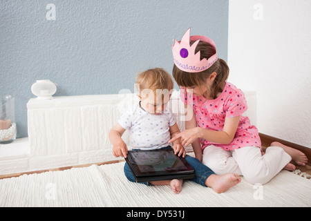 Girl watching over baby boy playing digital tablet - Stock Photo