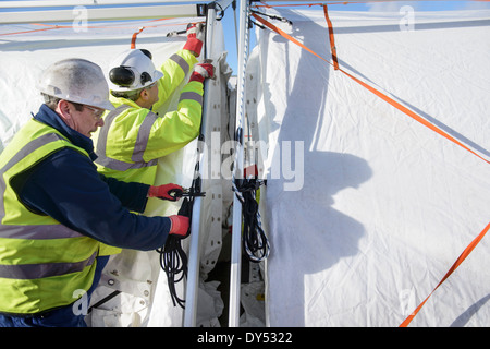 Emergency Response Team workers erecting tent control centre - Stock Photo