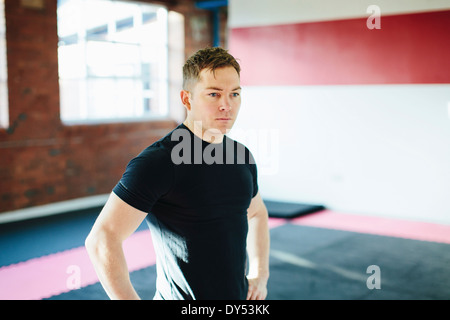 Man standing in gym with hands on hips - Stock Photo