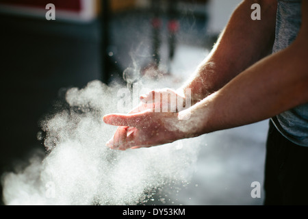Man putting chalk on his hands - Stock Photo