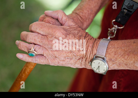 Close up of senior woman's hands holding walking stick - Stock Photo