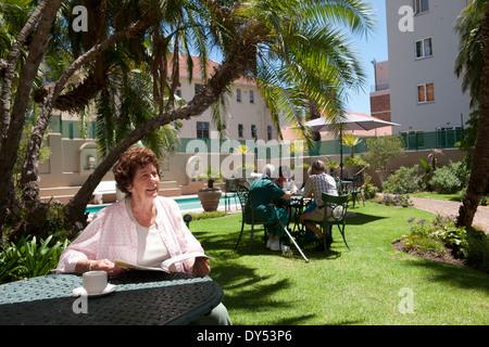 Senior woman having coffee in garden of retirement villa - Stock Photo