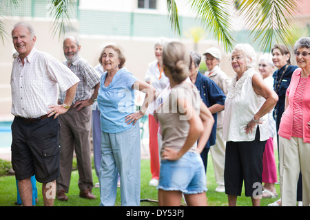 Large group of seniors exercising in retirement villa garden - Stock Photo