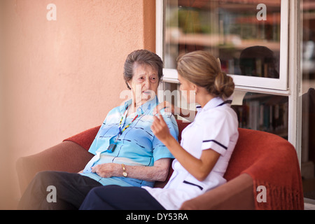 Care assistant chatting to senior woman on sofa - Stock Photo