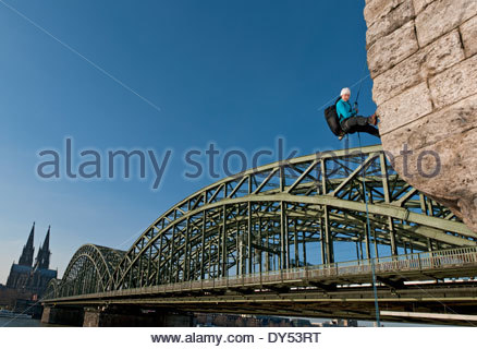 Female climber abseiling next to the Hohenzollern railway bridge, Cologne, Germany - Stock Photo