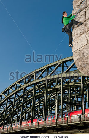 Mature female climber on man made wall next to the Hohenzollern railway bridge, Cologne, Germany - Stock Photo