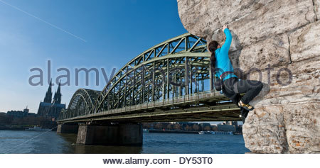 Female climber on man made wall next to the Hohenzollern railway bridge, Cologne, Germany - Stock Photo