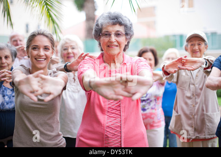 Medium group of seniors exercising in retirement villa garden - Stock Photo