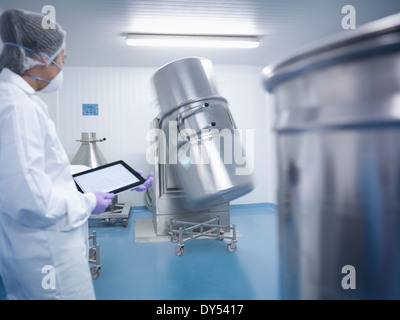 Worker holding digital tablet and watching ingredient mixing machine in pharmaceutical factory - Stock Photo