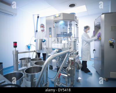 Workers with tablet pressing machine in pharmaceutical factory - Stock Photo