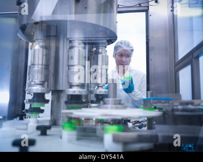 Worker inspecting products on production line in pharmaceutical factory - Stock Photo