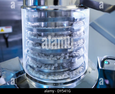Close up of tablets in tablet pressing machine in pharmaceutical factory - Stock Photo