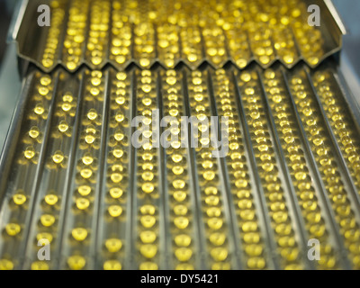 Rows of vitamin capsules in pharmaceutical factory - Stock Photo