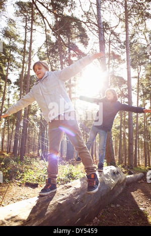 Twin brothers walking along fallen tree trunk in forest - Stock Photo