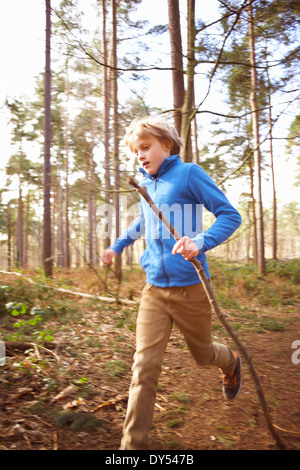 Boy running with a stick in woods - Stock Photo