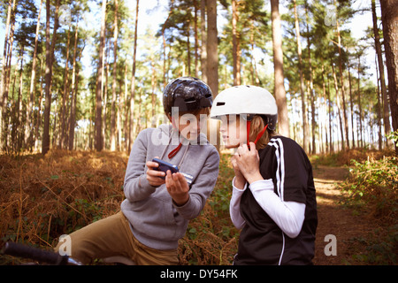 Twin brothers on BMX bikes in forest looking at smartphone - Stock Photo