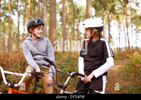 Twin brothers on BMX bikes chatting in forest - Stock Photo