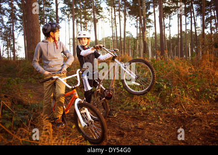 Twin brothers holding BMX bikes chatting in forest - Stock Photo