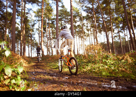 Twin brothers racing BMX bikes in muddy forest - Stock Photo
