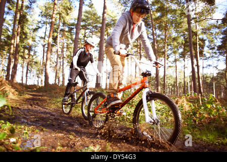 Twin brothers racing BMX bikes through muddy forest - Stock Photo