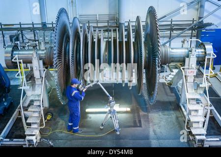 Engineer measuring low pressure steam turbine parts in repair works - Stock Photo