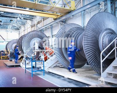 Engineers with low pressure steam turbines in repair bays in workshop - Stock Photo