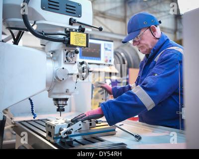 Engineer preparing lathe in steam turbine repair works - Stock Photo