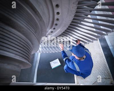 Engineer inspecting steam turbine in repair works - Stock Photo