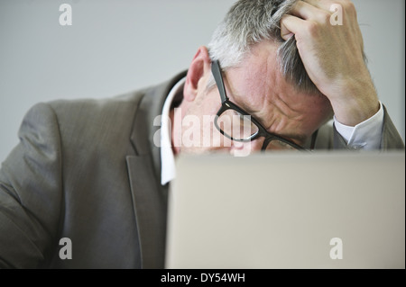 Stressed mature businessman in office - Stock Photo