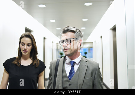 Business colleagues walking along office corridor - Stock Photo