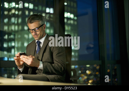 Businessman working late texting on smartphone - Stock Photo
