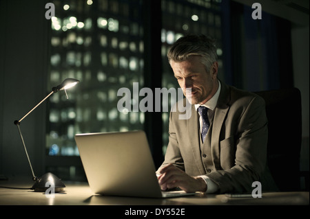 Businessman working late in office on laptop - Stock Photo