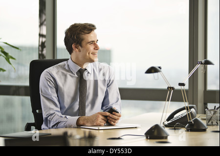 Young businessman sitting at desk in office - Stock Photo