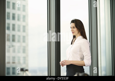 Portrait of businesswoman in high rise office - Stock Photo