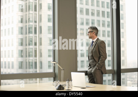 Businessman looking out of office window - Stock Photo