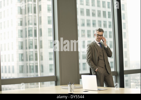 Portrait of businessman in high rise office - Stock Photo