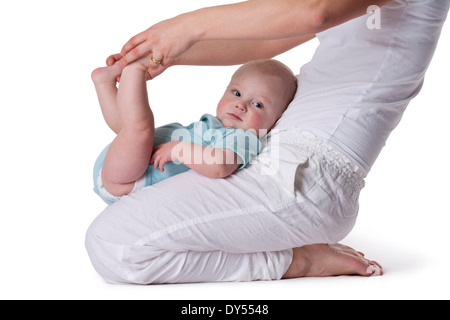 Baby boy doing excercises on mothers lap - Stock Photo
