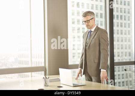 Businessman looking down at laptop on office desk - Stock Photo