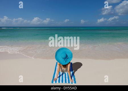 Young woman relaxing on beach with blue sunhat - Stock Photo