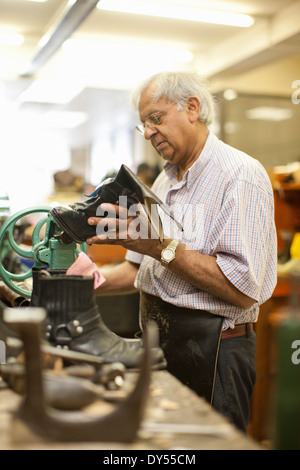 Cobbler repairing leather boot - Stock Photo