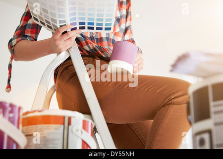 Teenage girl sitting on stepladders with coffee and swatch Stock Photo