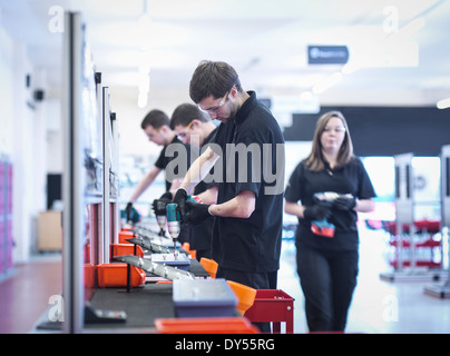 Apprentices working on training production line - Stock Photo