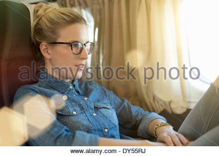 Portrait of young woman sitting on train - Stock Photo