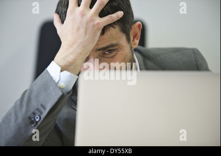 Young businessman looking stressed - Stock Photo