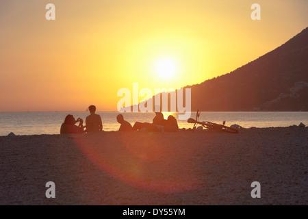 Small group of people watching sunset on beach, Vigan, Croatia - Stock Photo