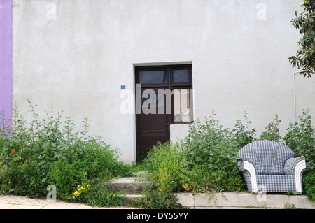 Old arm chair left outside an abandoned house Lapta North Northern Cyprus - Stock Photo